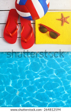 Flip flop shoes and sunglasses of young people near hotel pool - stock photo