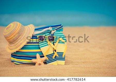 Flip-flops and bag on sandy beach against blue sea and sky background. Summer holiday concept