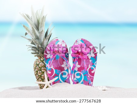 flip-flops and pineapple with tropical beach background, summer accessories - stock photo