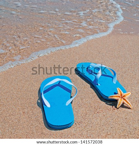 flip-flops and sea star by the shore - stock photo