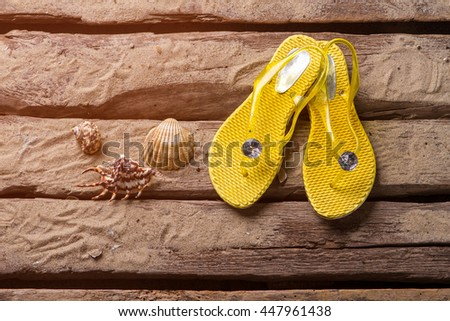Flip flops and seashells. Yellow flip flops on sand. Travel and explore the world. Exciting adventures are waiting. - stock photo