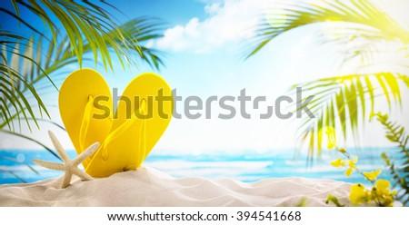 Flip-flops and starfish on beach - stock photo
