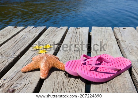 Flip flops and starfishes lying on an old swimming dock at the swimming lake - stock photo