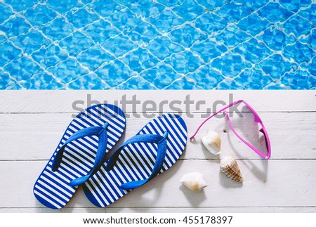 flip-flops and sunglasses on the swimming pool