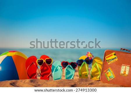 Flip-flops, beach ball and suitcase on the sand. Summer vacation concept - stock photo