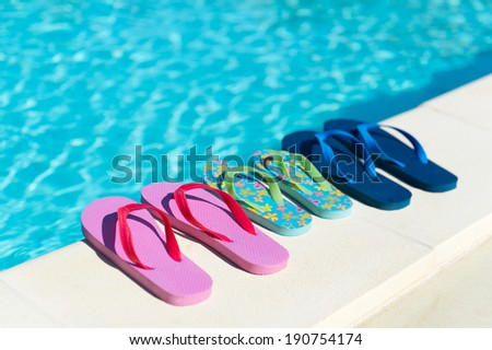 Flip flops for him and her at the swimming pool - stock photo