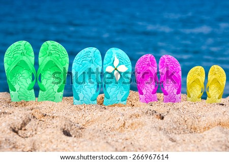 Flip flops of a family of four in the sand of a beach - stock photo