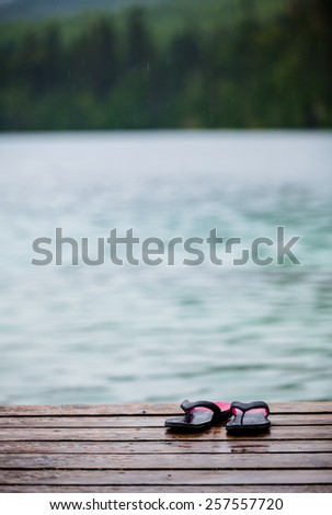 Flip flops on a Dock in front of a Turquoise Water Lake in the Wild Nature - stock photo