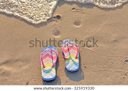 flip-flops on beach with footprints in sand and frothy surf - stock photo