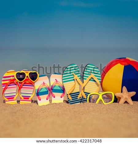 Flip-flops on sandy beach against blue sea and sky background. Summer vacation concept - stock photo