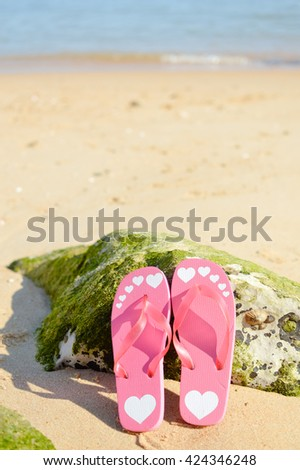 Flip flops on sandy ocean beach background outdoors, warm and nice weather for relaxation - stock photo