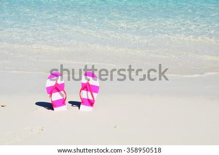 Flip-flops on the beach - stock photo