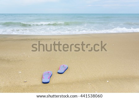 Flip-flops on the beach on sea background. - stock photo