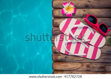Flip-flops on wood against blue water background. Summer holiday concept - stock photo