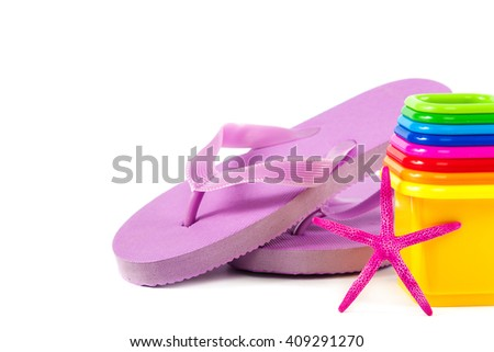 Flip flops, sand toys and seashells isolated on a white background. The concept of a beach holiday. - stock photo