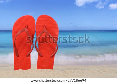 Flip Flops sandals in summer on beach and vacation with sand and copyspace - stock photo