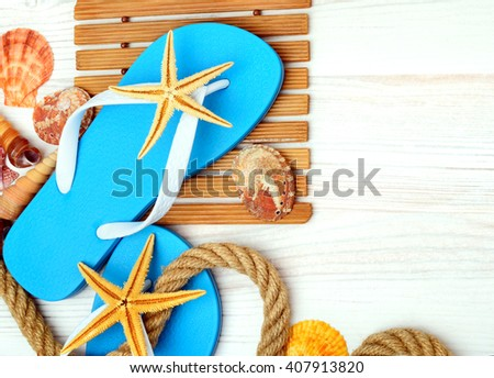 Flip-flops, starfish and seashells on a wooden background.