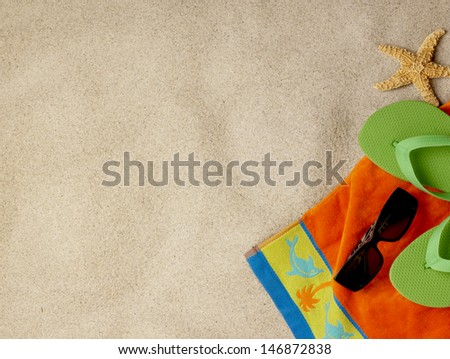 Flip flops, sunglasses, towel and shells on the beach - stock photo
