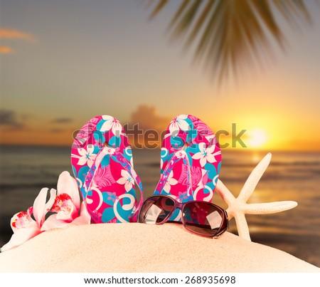 flip-flops with tropical beach, sun set background, summer accessories - stock photo