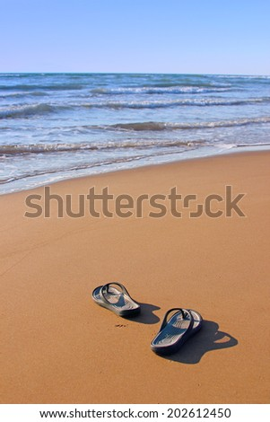 Flipflops on a sandy beach. Summer vacation concept - stock photo