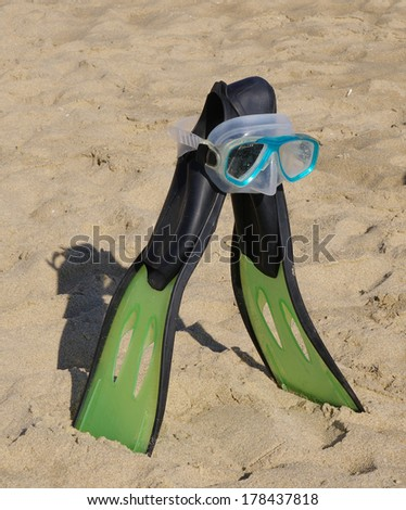 Flippers and diving mask on beach