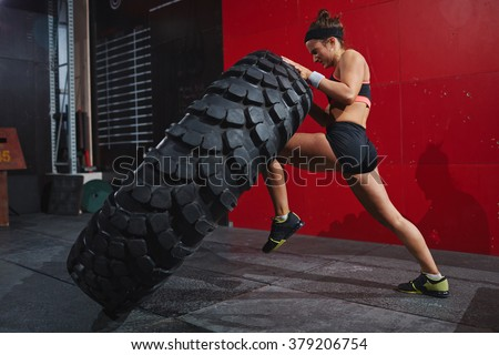 Flipping tyre in gym - stock photo
