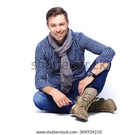 Flirtatious man sitting on the floor - stock photo