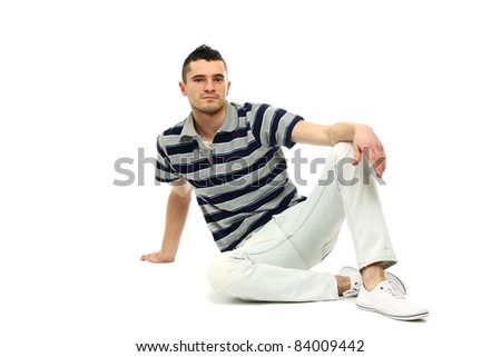 Flirtatious man sitting on the floor isolated on white background - stock photo