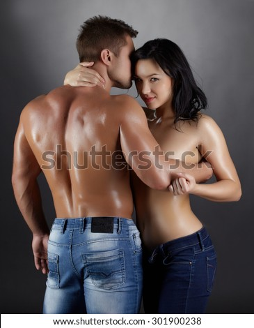 Flirtatious woman and strong man posing in studio - stock photo