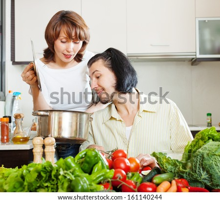 Flirting couple cooking together in home kitchen