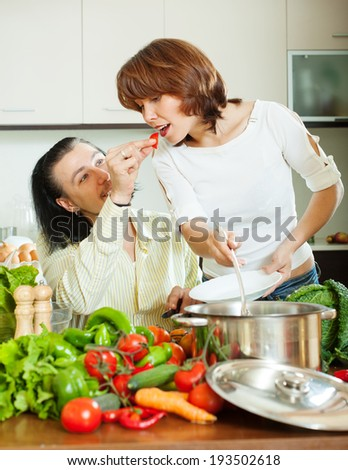 Flirting couple cooking with vegetables in home