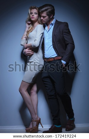 flirting fashion couple standing embraced in studio - stock photo