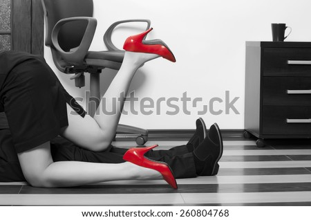 Flirting. Low section of business couple getting intimate on floor in office - stock photo