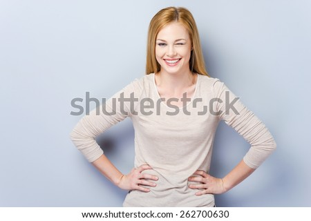 Flirting with you. Beautiful young woman winking and holding hands on hips while standing against grey background   - stock photo