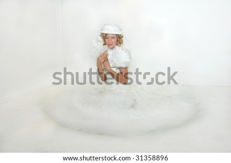 Flirty and feathery fans, hat and netting, and strapless gown.  Bride sits on white carpet in white room. - stock photo