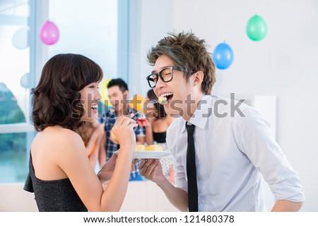 Flirty girl giving piece of cake to a boy - stock photo
