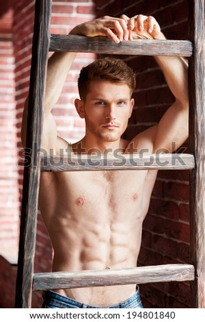 Flirty handsome. Handsome young shirtless man leaning at the wooden ladder and looking at camera while standing near the brick wall - stock photo
