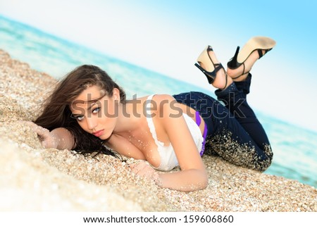 Flirty young brunette wearing shirt and jeans lying on the beach - stock photo
