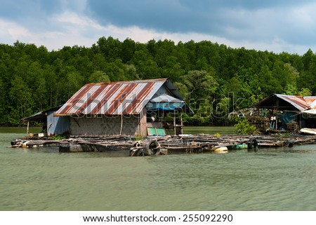 Float fishing village on tropical river with trees on background - stock photo
