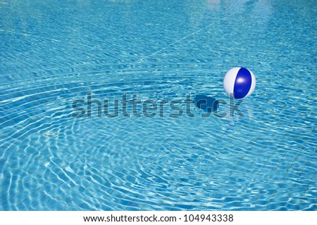 Floating blue and white beachball in swimming pool - stock photo