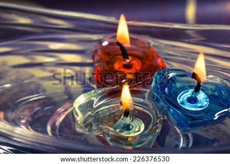 floating burning candles in glass aroma bowl, retro - stock photo
