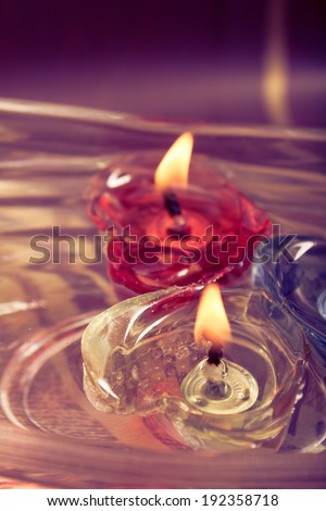 floating burning candles in glass aroma bowl - retro effect - stock photo