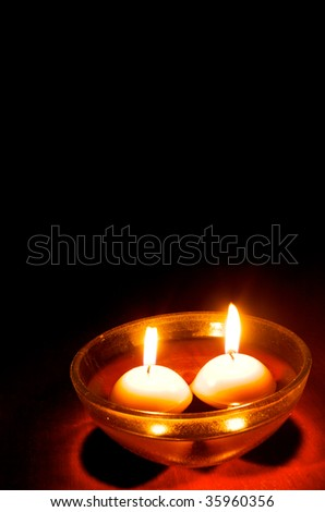 Floating candles on wooden table with black background - stock photo