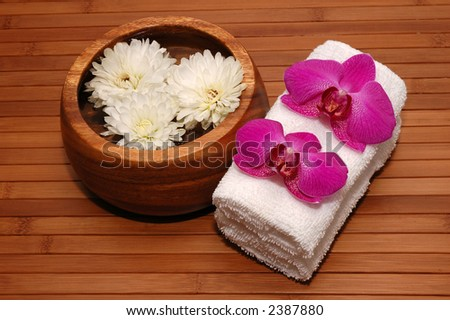 Floating chrysanthemum, towels and orchids on a bamboo mat