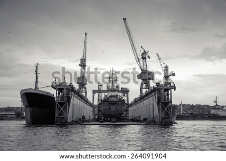 Floating dry dock with old ship under repair inside, retro stylized black and white photo, front view - stock photo