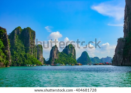 Floating fishing village near rock islands in Halong Bay, Vietnam, Southeast Asia - stock photo