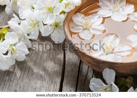 Floating flowers ( Cherry blossom)   in  clay  bowl.  - stock photo