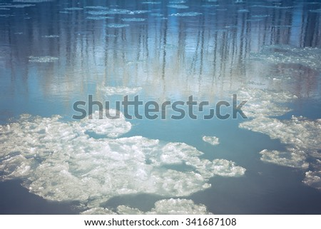 Floating ice chunks in an Alaskan river in fall before freeze-up with tree reflections and creative coloration. - stock photo