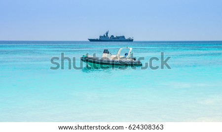 Floating military speed patrol cruiser boat and warship with helicopter. Seascape view in Andaman sea, Southeast Asia.