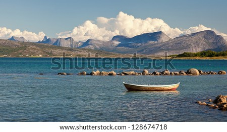 floating old boat on mountain lake - stock photo